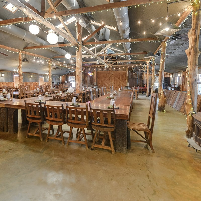 interior of barn house with long banquet tables and chairs