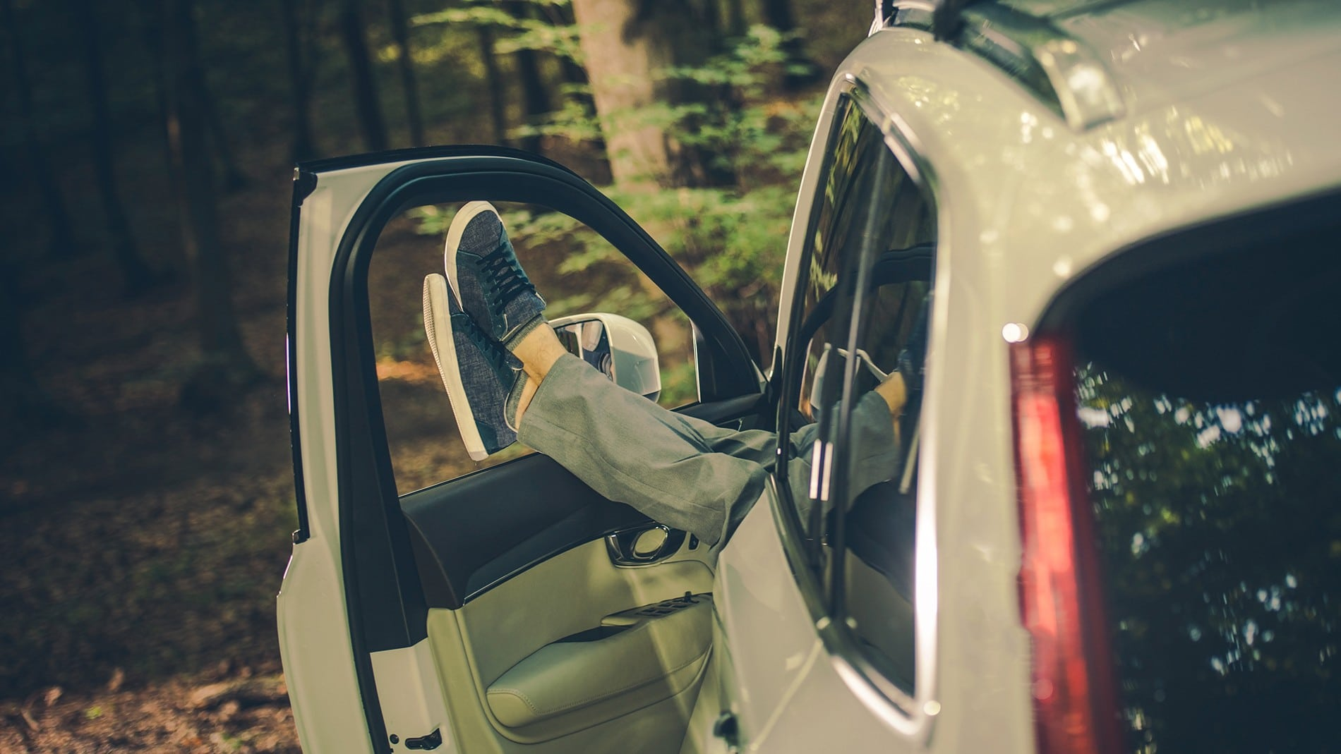 person relaxing with feet resting on door of vehicle