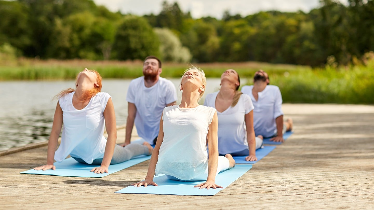 group of people practicing yoga on dock beside river