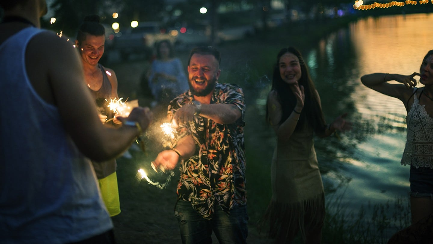 friends having fun with fireworks at night