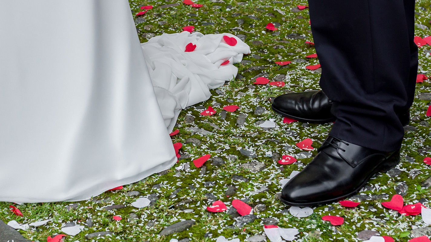 bride and groom standing on green grass with red and white paper hearts