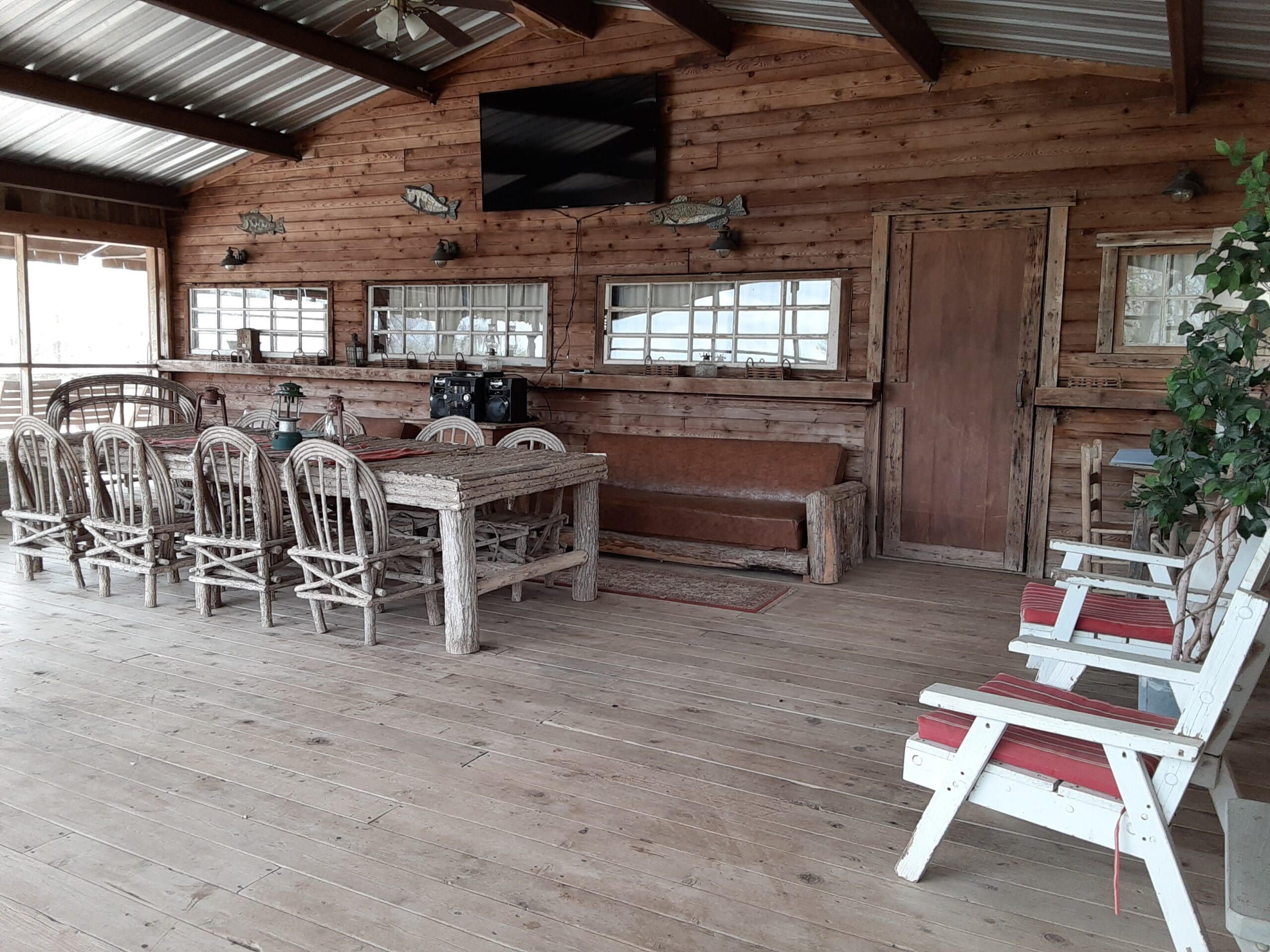 interior of boat house with screen walls and tables and chairs