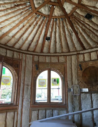insulated curved walls with arched windows and peaked ceiling in custom home under construction
