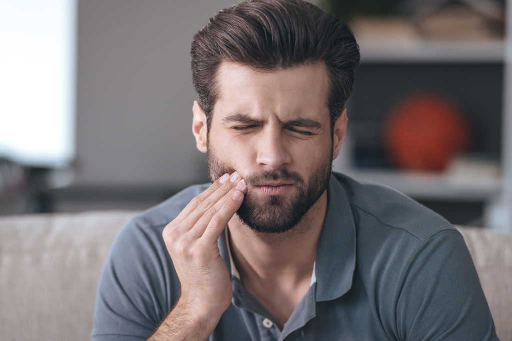 Toothache. Frustrated young man touching his cheek and keeping eyes closed while sitting on the couch at home and hoping to get an emergency dentist appointment at Smiles of Beverly Hills.