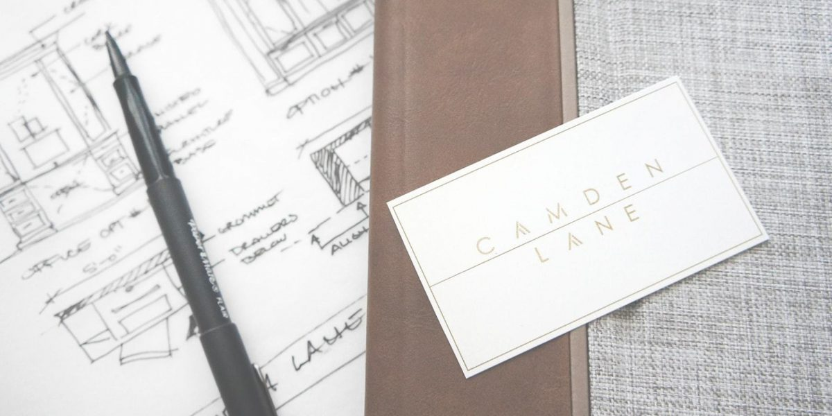 A Camden Lane Interior business card with day planner and design sketched in the background