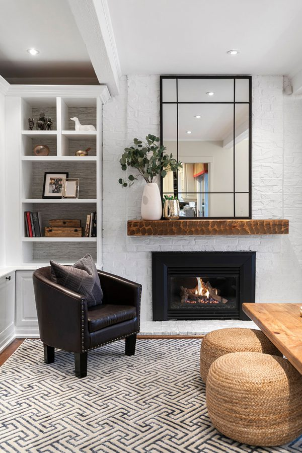 We painted out the brick and added a wall-mounted mantle that ties in the existing coffee table