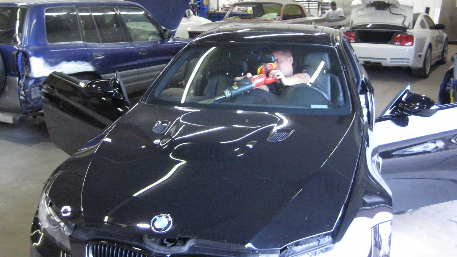 Man installing windshield on a black car