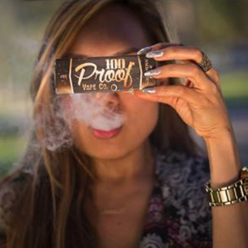 Girl reading Label of 100 Proof E Liquid Box and Vaping
