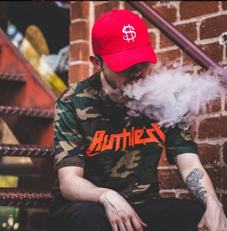 Guy in Ruthless Shirt Vaping Eliquid