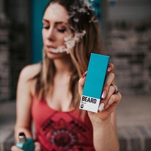 girl vaping beard vape eliquid and blowing clouds