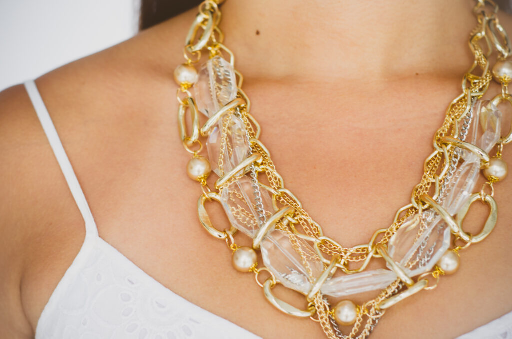 Close up of intricate chain and mesh statement necklace on woman