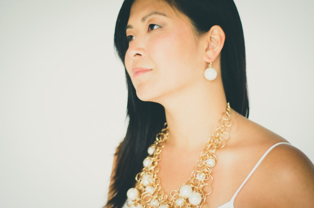 Woman wearing white and gold statement necklace with matching earrings