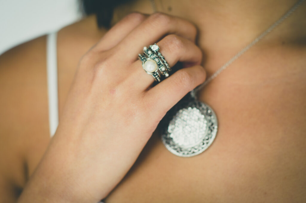Close up of statement necklace on woman with matching pearl ring on hand