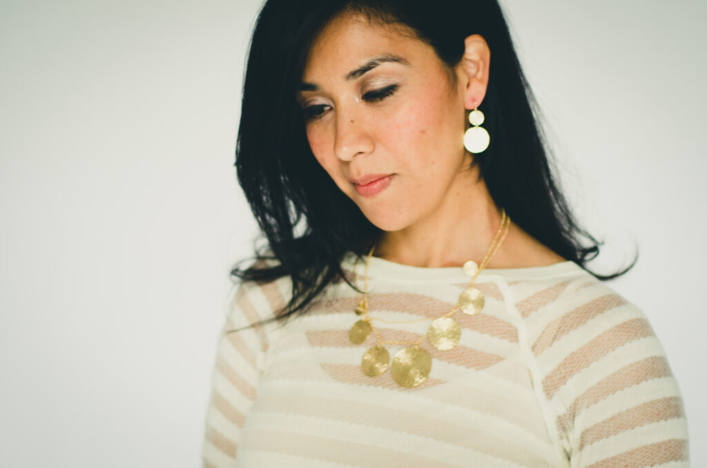 Woman in striped shirt wearing gold statement necklace and earrings