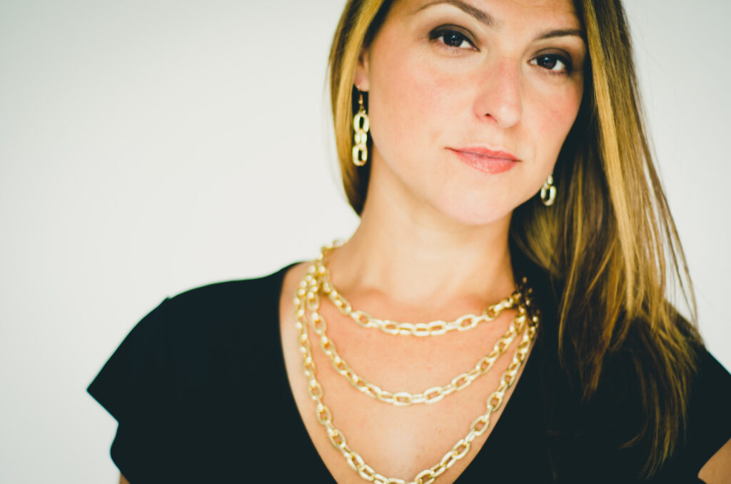Woman wearing looped chain necklace and matching earrings