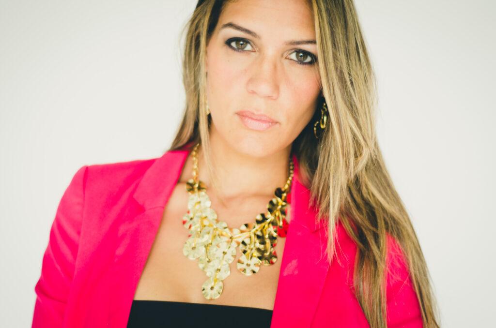 Woman in pink blazer wearing gold statement jewelry