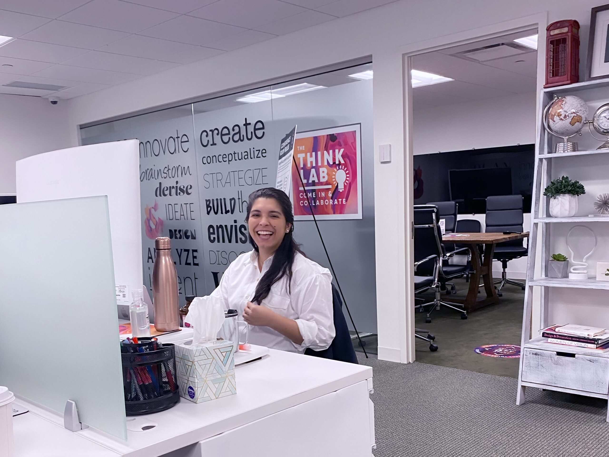 Copy & Art employee smiles at her desk at the White Plains office