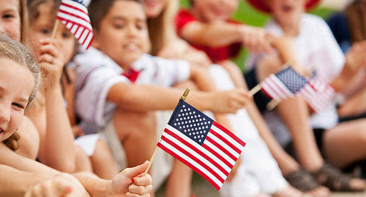 Close-up photo of a group of children sitting down holding miniature american flags