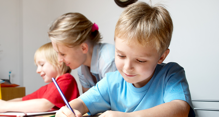 Image of a smiling child, sitting and writing, with a teacher and other child in the background who is doing the same