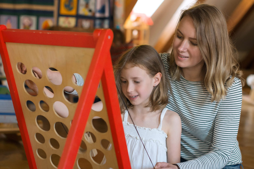Young girl and her mother playing an game on a board with holes in it