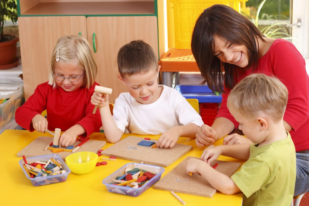 Smiling teacher sitting at a table with three children playing with blocks