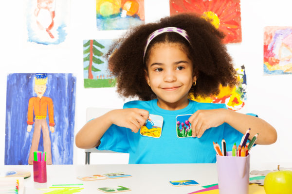 Girl holding pictures sitting at a table in front of a wall full of children's drawings