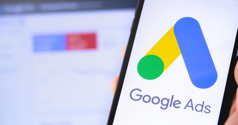 phone with Google Ads logo and laptop in the background