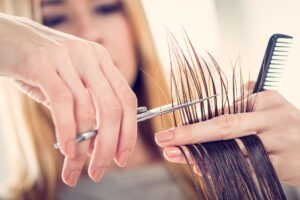 Close-up of a hairdresser cutting the hair of a woman. Selective focus.