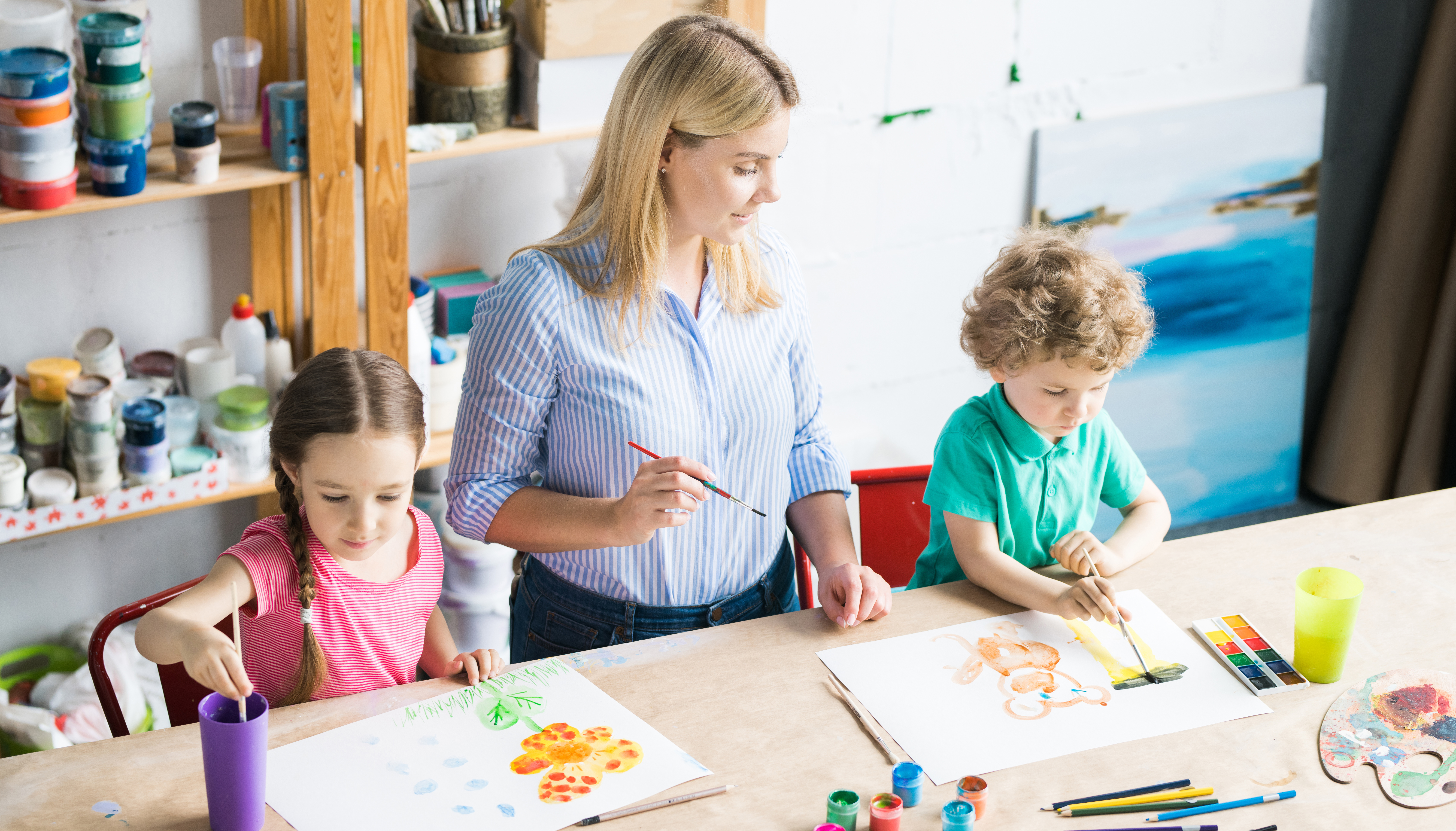 Children drawing a picture with paints and young teacher assisting them