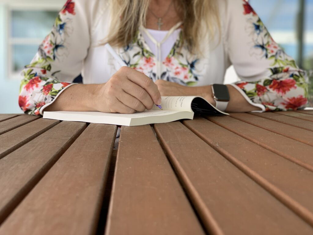 woman writing in Grateful Faith Gratitude Journal at wood table