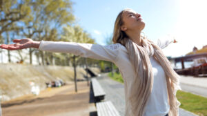 Woman outside with arms raised as giving gratitude to God