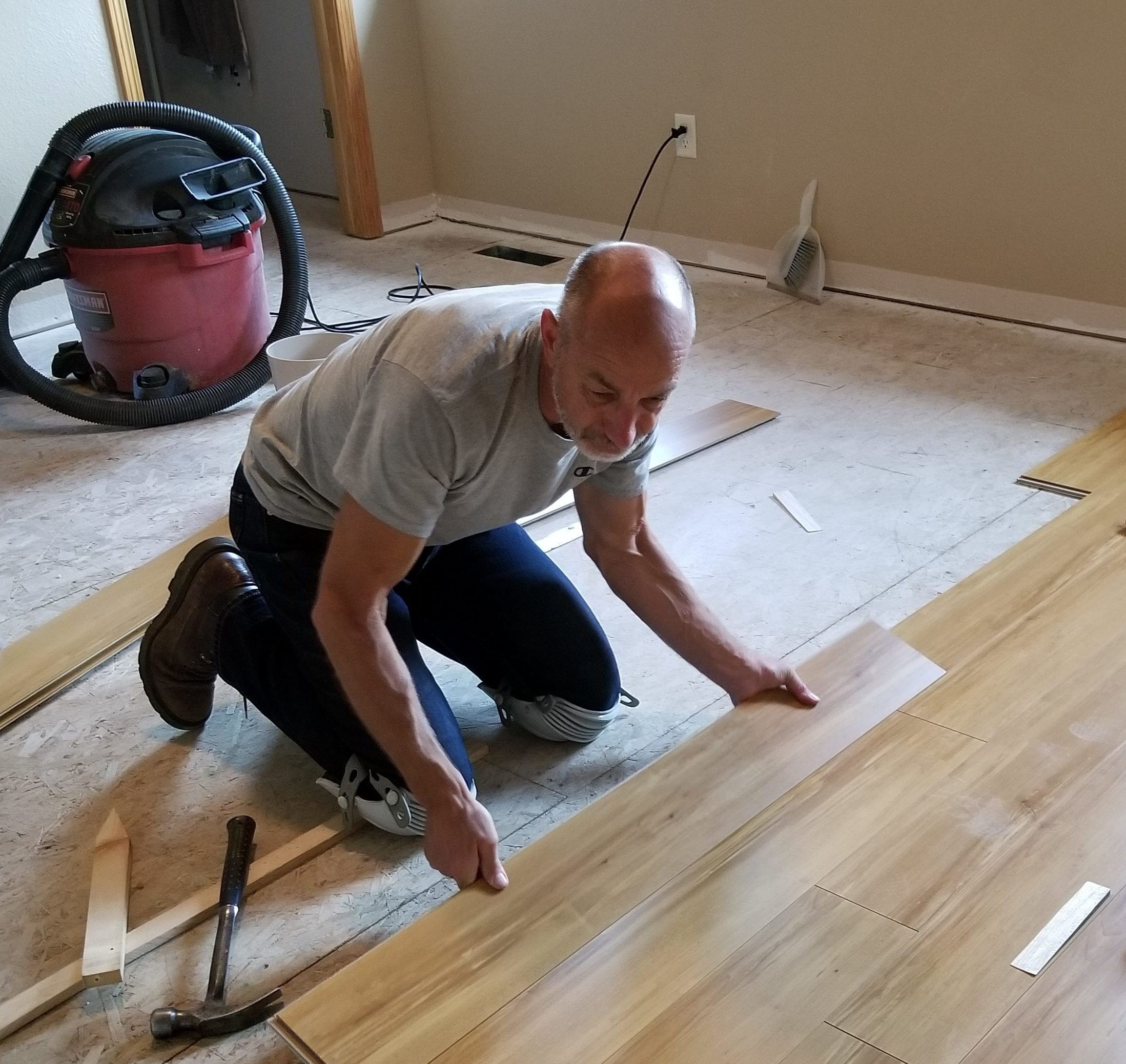This is a photo of Dean installing new flooring in a master bedroom.