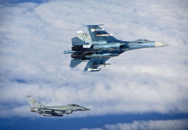 Royal Air Force Eurofighter Typhoon (bottom) escorts Russian Air Force Su-27 Flanker (top) over the Baltic in June 2014. (Photo: Courtesy of RAF/WikiCommons)