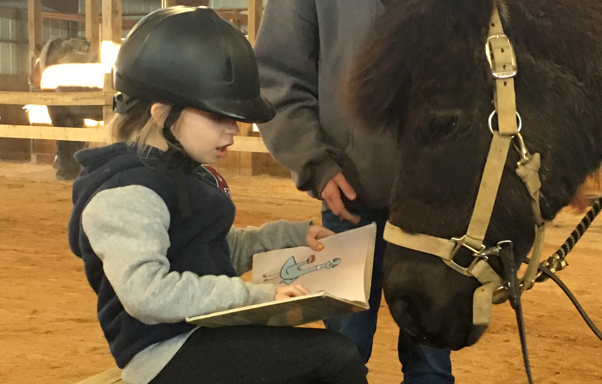 child reading to a black pony