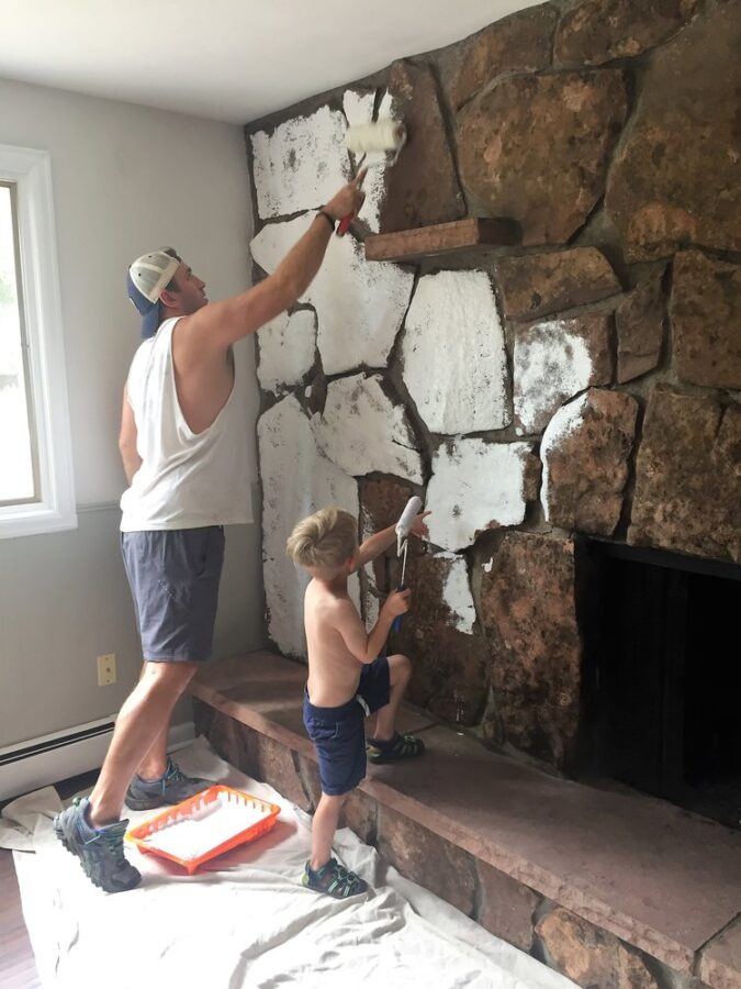 Thomas and Chris painting the rock fireplace with Kilz.