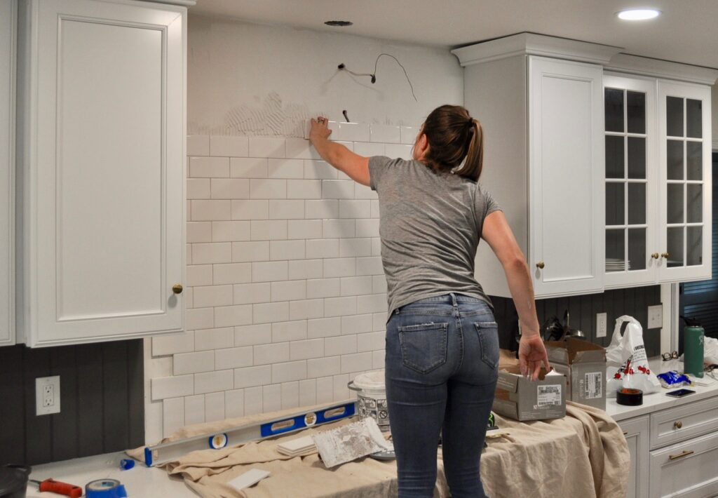 Installing the subway tile behind the kitchen range
