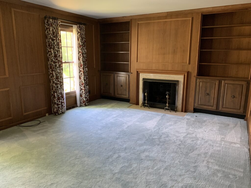 The formal office in our new home with wood paneling, a fireplace and built in bookcases.