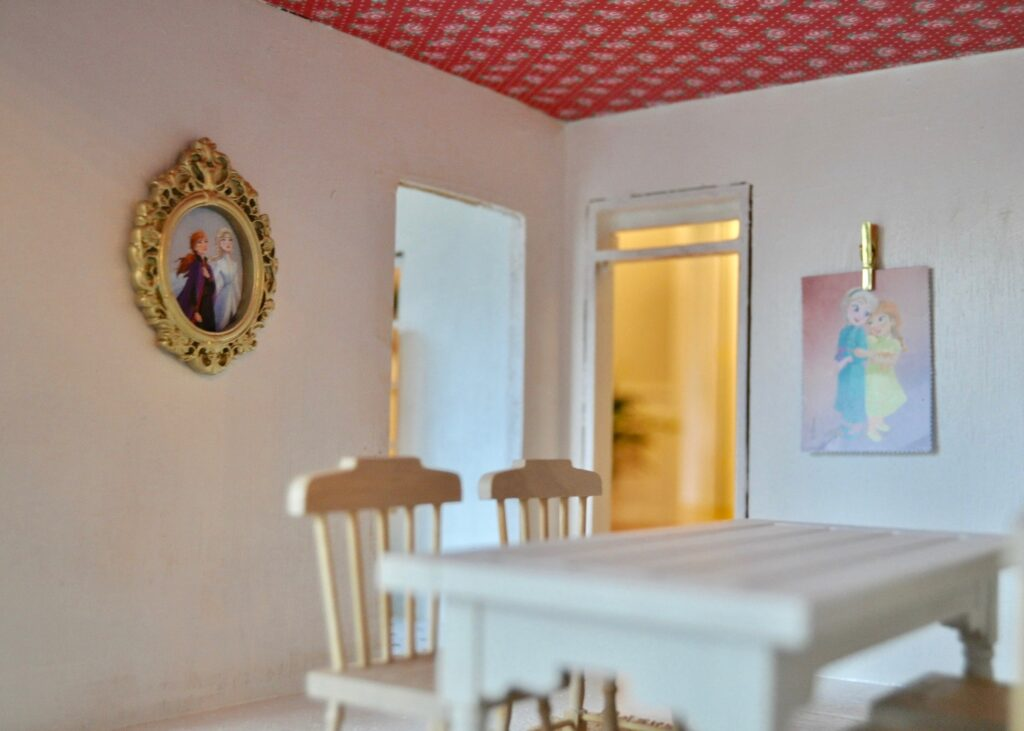Wallpapered ceiling and Frozen artwork in the dollhouse