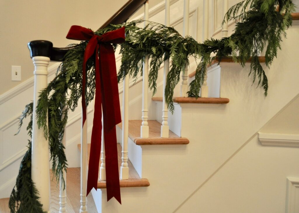 Garland and red velvet ribbon on the staircase