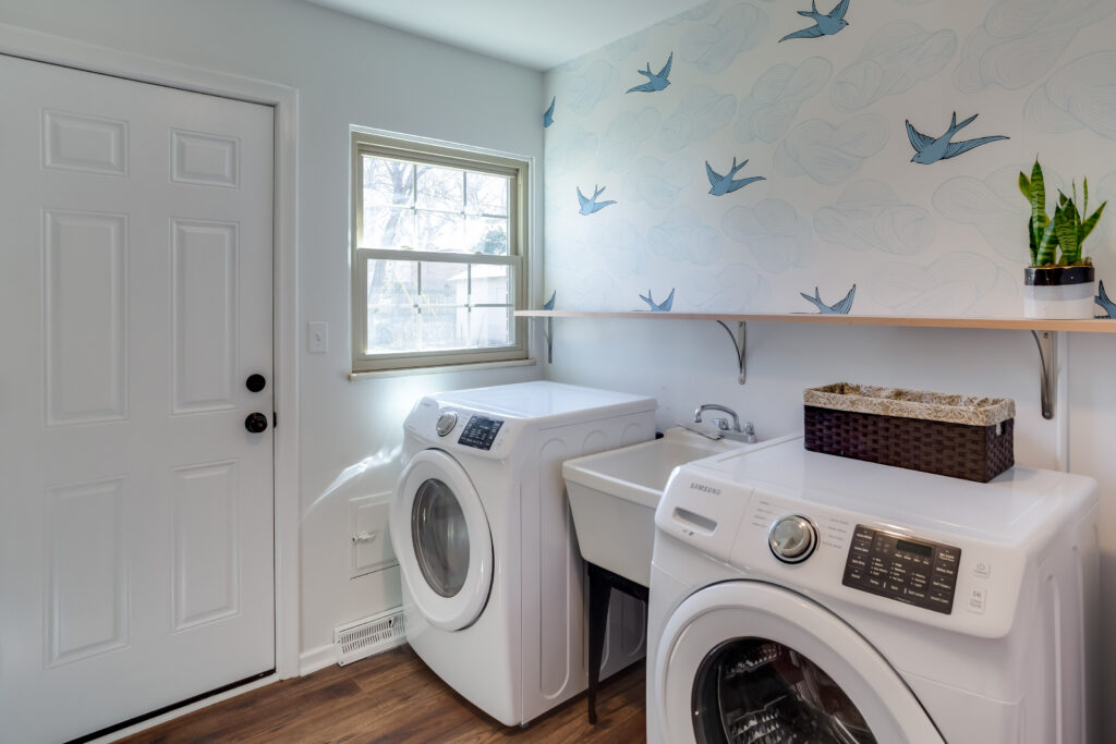 Laundry room with trendy wallpaper