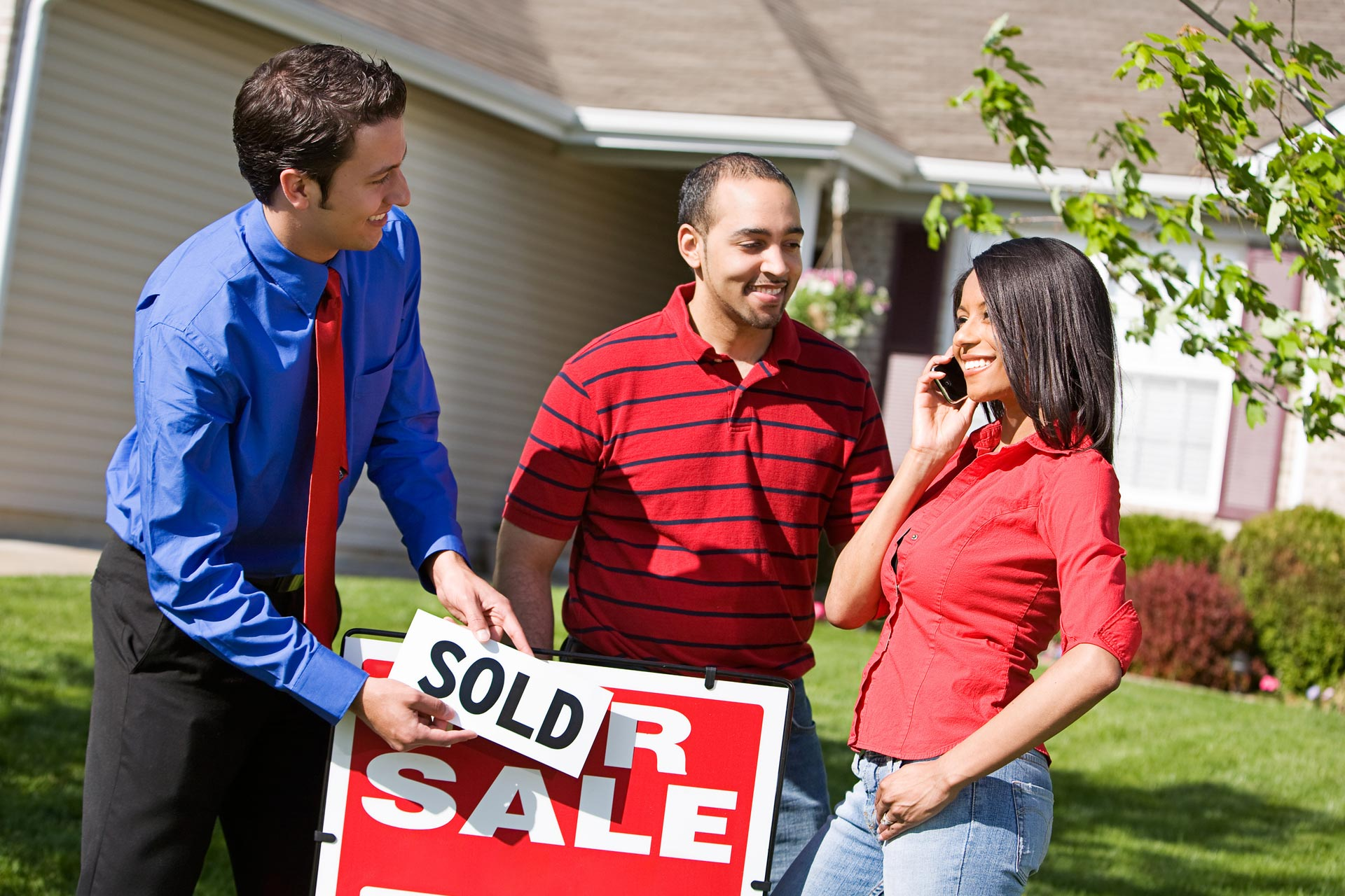 Agent and happy new home owners next to a sold sign