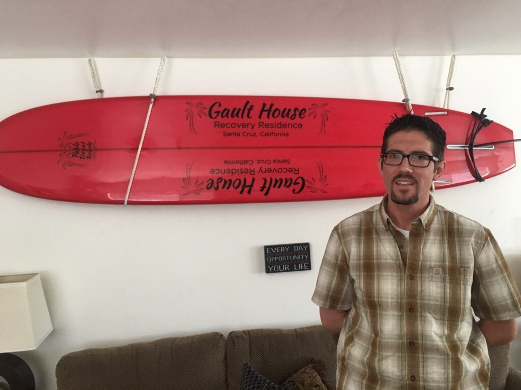 Stefan with Red Surfboard in Lounge at Gault House A Sober Living Home - Responsible Recovery