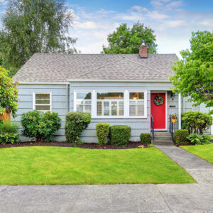 Exterior of small American house with blue paint and red entrance door. Northwest, USA