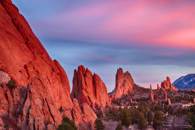 """Garden of the Gods with a beautiful colorful sunset sky.  The Garden of the Gods red rock formations were created during a geological upheaval along a natural fault line millions of years ago. Archaeological evidence shows that prehistoric people visited Garden of the Gods about 1330 BC. About 250 BC Native American people camped in the park.  Garden of the Gods is a public park located in Colorado Springs on the north part of Colorado City, Colorado, USA. It was designated a National Natural Landmark in 1971.  How the Garden of the Gods was Named - In 1859, gold was discovered in the South Park area of Colorado, and """"Pikes Peak or Bust"""" became a popular slogan as vast numbers of fortune seekers headed west. Boom towns were created overnight; over 100,000 people arrived in the region in just one year! The Pikes Peak area became a funnel of humanity since it sat at the foot of Ute Pass, the only accessible route to South Park. The Pass funneled gold seekers from three major routes across the plains.  It was August of 1859, when two surveyors started out from Denver City to start formal action in locating a townsite, soon to be called Colorado City. While exploring nearby locations, they came upon a beautiful area of sandstone formations. M. S. Beach, who related this incident, suggested that it would be a """"capital place for a beer garden"""" when the country grew up. His companion, Rufus Cable, a """"young and poetic man"""" exclaimed, """"Beer Garden? Why this is a fit place for the Gods to assemble. We will call it the Garden of the Gods."""" It has been so called ever since.   Colorado Fine art nature landscape photography poster prints, decorative canvas prints, acrylic prints, metal prints, corporate artwork, greeting cards and stock images by James Bo Insogna (C)   - All Rights Reserved.   Please feel Free to share our links, with Family or Friends who may also enjoy them.   If you like my Art Gallery, please spread the word and press the Pinterest, FB, Google+, Twitter or SU"""