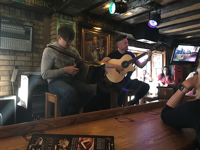 Two male guitarists performing at a restaurant
