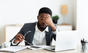 Fatigued man holding his head at a computer.