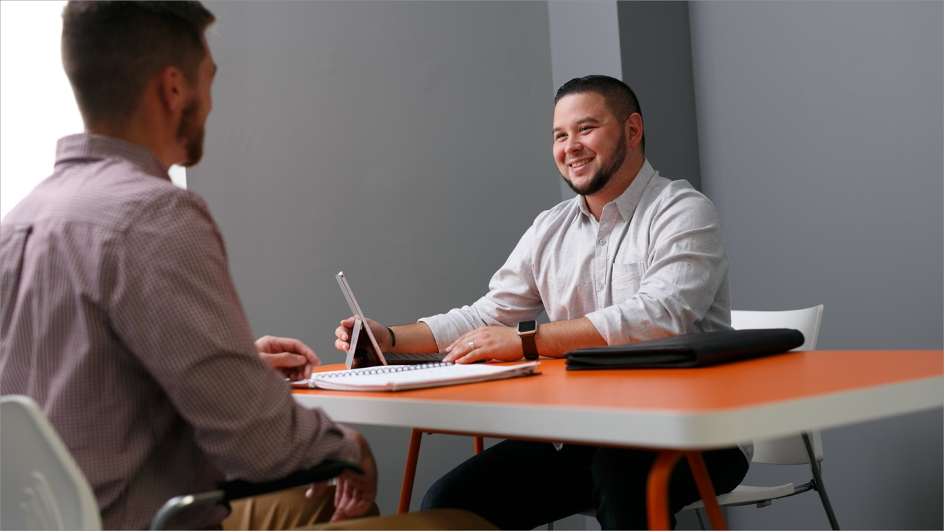 internship interview questions: Man smiling at an interviewee from across the table