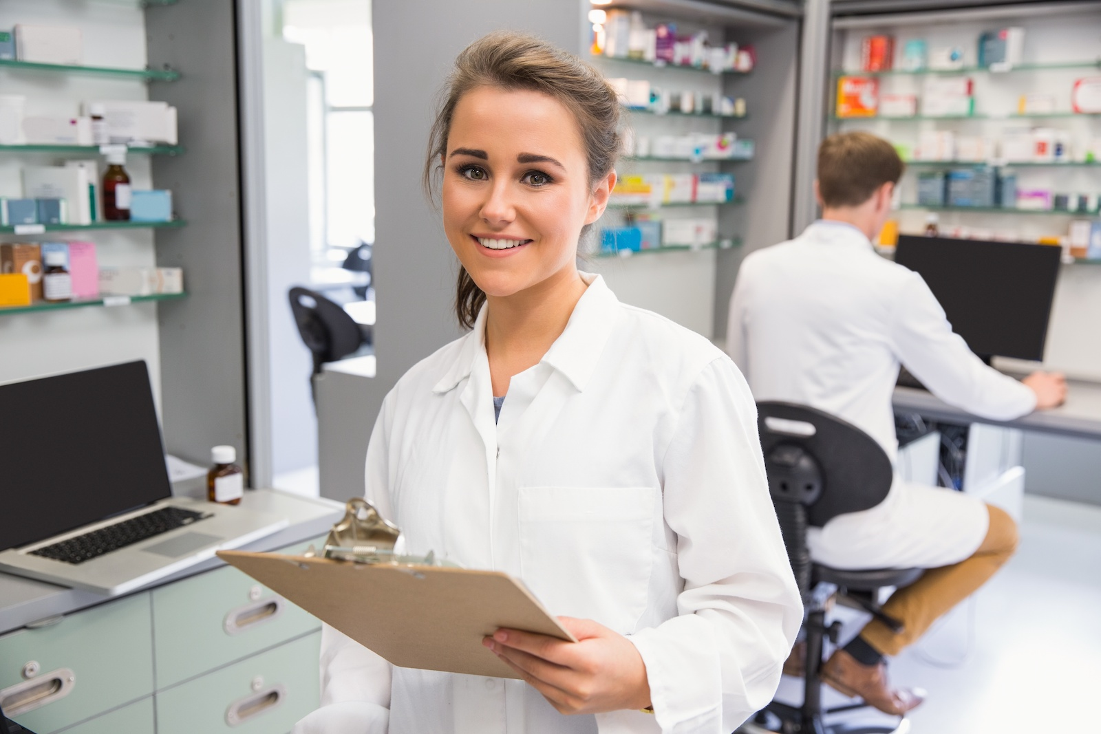 internship: Pharmacy intern smiling at the camera while holding a clipboard