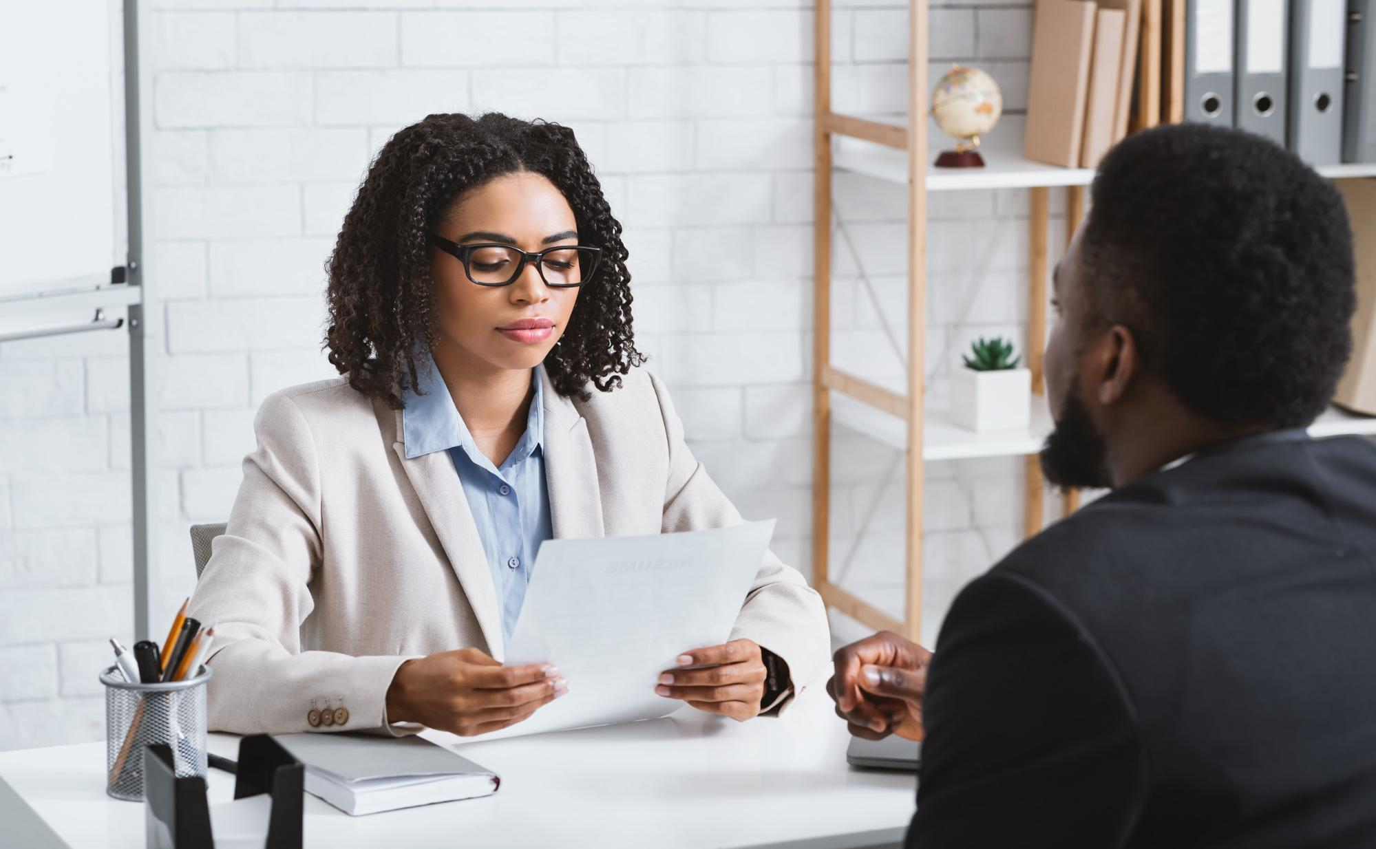 internship interview questions: Woman reading a man's resume during an interview