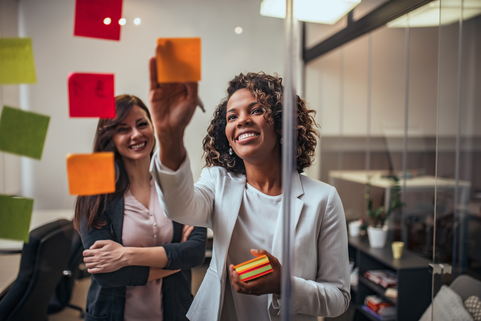 internship: Woman writing on sticky notes on a glass wall with a female colleague looking from behind